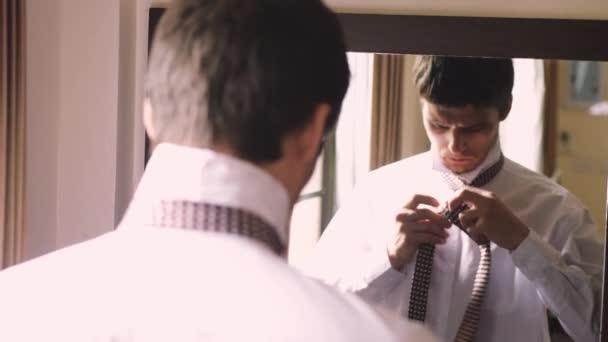 Giovane uomo alla moda in camicia bianca si erge dallo specchio di legare una cravatta. 3840 x 2160, 4K