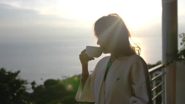 Young beautiful woman wears bathrobe drinks coffee in the morninig during amazing sunrise stands on the terrace of her villa enjoying the moment. slow motion. 3840x2160, 4k