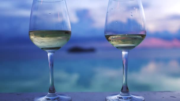 Glasses of white wine stands next to infinity swimming pool by amazing sunset view.