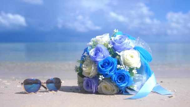 Bouquet beautiful flowers and sunglasses on the beach white sand tropical paradise island on sea water ocean background and cloudy sky changes focus to the sea. slow motion. 3840x2160. 4k