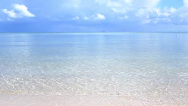 Panoramatický krajinu a úžasné tropické pláže. Vlny oceánu a zamračená obloha pozadí. Bílý písek a křišťálově modré moře. Zpomalený pohyb. 3840 x 2160