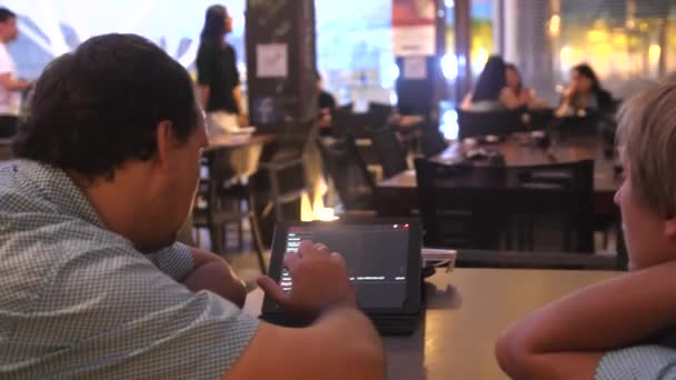 Singapur, Singapurská republika, 25 května 2018. Dva muži zákazníky posouvání Tablet Menu v restauraci. 3840 x 2160