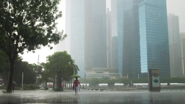 Singapur, 26 května 2018. Silný déšť v centru Singapuru. Žena s deštníkem procházky v dešti. 3840 x 2160