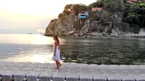 Aerial view of young brunette pretty woman in white dress walking on bridge among the sea on tropical island during amazing sunset. 1920x1080