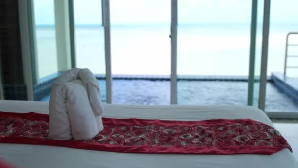 Hotel bed in luxury hotel room with white bedding on jacuzzi and the sea on foreground. Welcome resort decor. The towel is made in the form of an elephant. slow motion. 3840x2160
