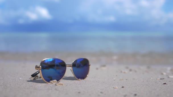 Reise- und Urlaubskonzept. blaue Sonnenbrille an einem weißen Strand am Meer. Faulheit türkisfarbenes Meer im Hintergrund mit Kopierraum. 3840x2160