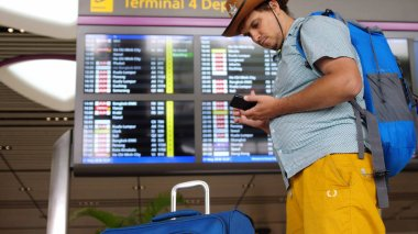 Singapore, 27 may 2018. Young handsome international airport tourist passenger in hat uses mobile phone stands with backpack and suitcase at schedules of departure board of aircraft. 3840x2160