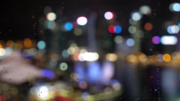 Abstract blurred light with office building and reflection night view on Singapore. changes focus to architecture of the city through the drops during rain. 3840x2160