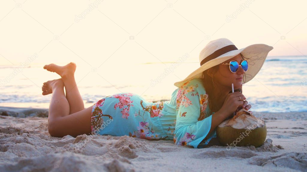 Young tourist pretty woman in sunglasses and the hat lying on tropical paradise sandy beach and drinks coconut juice during beautiful sunset