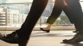 Národy metrů chůze na přechodu pro chodce na náročném dni v centru města za slunečného dne na silnici na pozadí