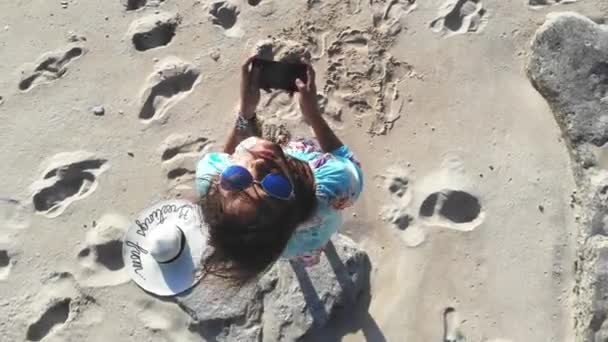 Young brunette pretty woman controls piloting drone copter using console holding phone at ocean beach. Smart girl operates fly quadcopter. 3840x2160, 4k