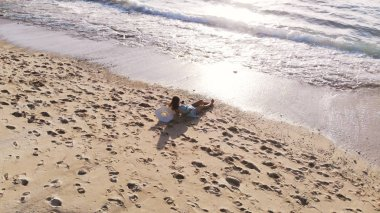 Aereal drone view of young pretty woman is lying on tropical paradise sandy beach and drinks coconut juice during beautiful sunset