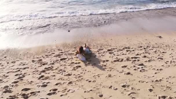 Letecká dron pohled mladá brunetka žena v sluneční brýle ležící na pláži tropického ráje a používá mobil během krásný západ slunce. 3840 x 2160
