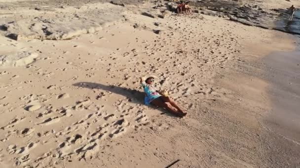 Aereal drone view of young pretty woman in sunglasses and the hat lying on tropical paradise sandy beach uses mobile phone during beautiful sunset. 3840x2160