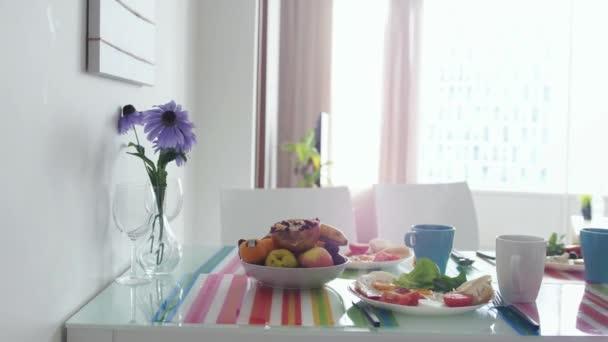 Ranní snídani s kyticí květin a talíř s ovocem v kuchyni apartmánu. Zpomalený pohyb. 3840 x 2160