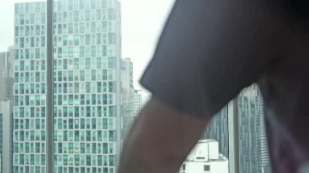 Mladý podnikatel obdivovat výhled z okna v bytě podnikání. 3840 x 2160