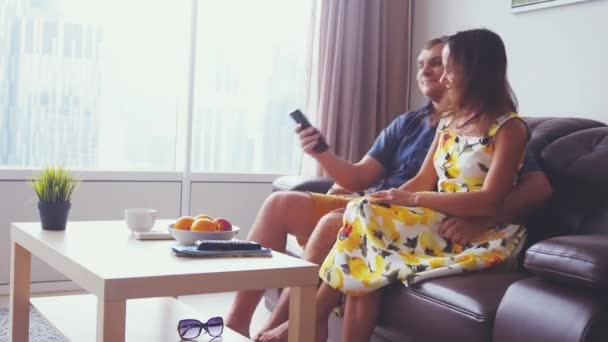 junges hübsches Paar vor dem Fernseher im Wohnzimmer in der Wohnung am Panoramafenster. 3840x2160
