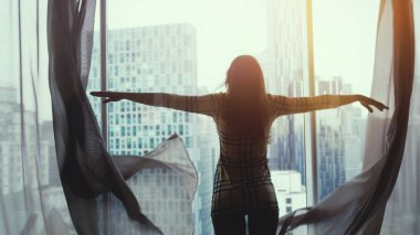 Silhouette of young brunette woman unveil curtains and admires sunset view from the window at home in apartment.