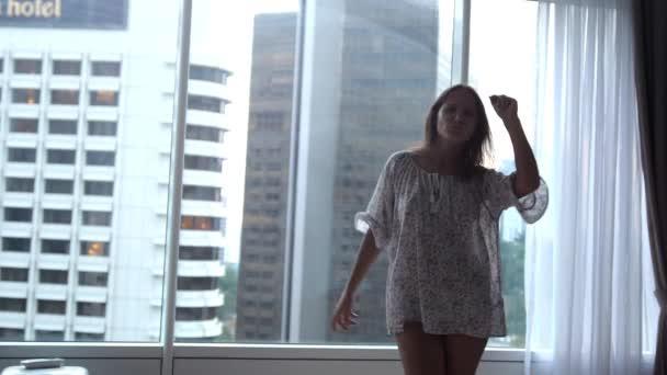Bruneta žena radostné tance poblíž panoramatická okna, poslech hudby v bytě s výhledem na město z okna. Zpomalený pohyb. 3840 x 2160