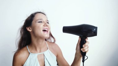 Beautiful young happy woman sings song while using hairdryer on a white background