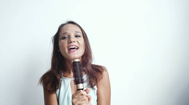 Young pretty brunette joyful woman sings song while holding a comb on a white background.