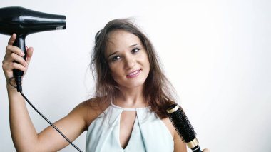 Beautiful young happy woman using hairdryer on a white background