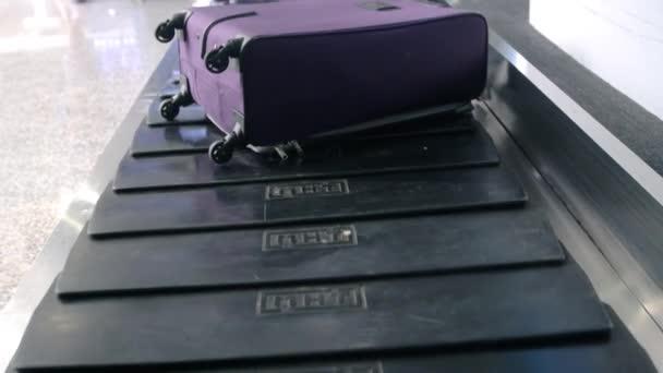 Letiště zavazadel se zavazadly točí kolem dopravníku. Taveler rozmazané muž bere její kufr z dopravníku na letišti a listy. Detailní záběr na něj ruce. 3840 x 2160