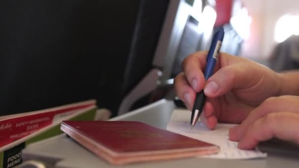 Passenger with passport is filling in the migration or arrival cards in the plane while flight. 3840x2160