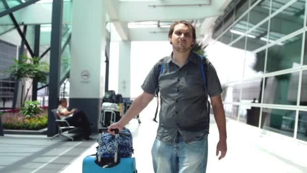 Mladý muž, tahání kufru v moderní letiště terminál. Cestování člověk odcházel s jeho zavazadly