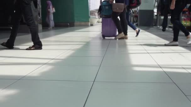 Detailní záběr nohou k nepoznání lidí s zavazadla v terminálu letiště. Zpomalený pohyb. 3840 x 2160