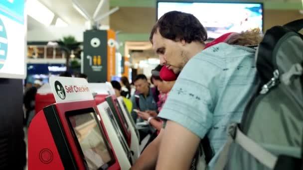 Singapur, 13 července 2018. Dva cestující muži s batohy odbavení u svépomoci přepážky na letišti. 3840 x 2160