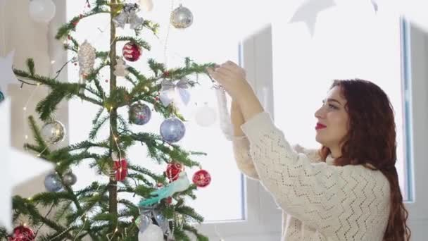 Young woman red-haired decorating christmas tree with toys by the window. slow motion. 3840x2160