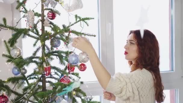 Mladá krásná žena, zdobení vánočního stromu s hračkami oknem. Zpomalený pohyb. 3840 x 2160