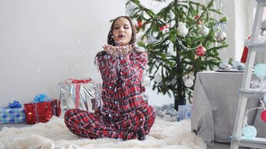 Young pretty brunette woman blowing confetti by fir-christmas tree sits on a rug and the window in studio