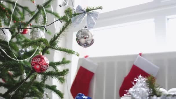 Stylový bílý vánoční interiér dekorovaný jedle a zablokuje ponožky oknem. Zpomalený pohyb. 3840 x 2160