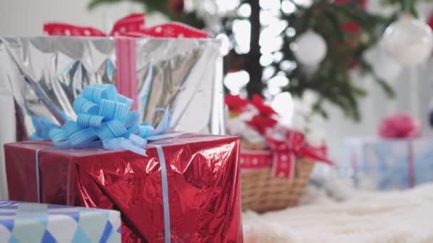 Elegáns díszdobozok és díszített, homályos fenyő és a Santa Claus a háttérben. lassú mozgás. 3840 x 2160