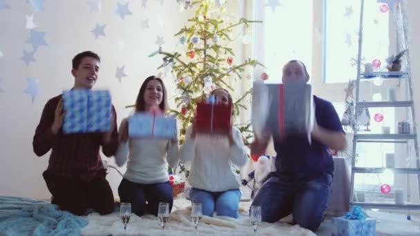 Fiatal mosolygó meg ünneplő karácsony karácsonyfa előtt ül, gazdaság díszdobozok, és amely dobozok, hogy a kamera. Fogalmának ünnepli az új év. 3840 x 2160