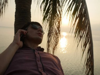 Young handsome happy man in sunglasses sits on a palm tree on a background of beautiful sunset on the seashore and talks on mobile phone