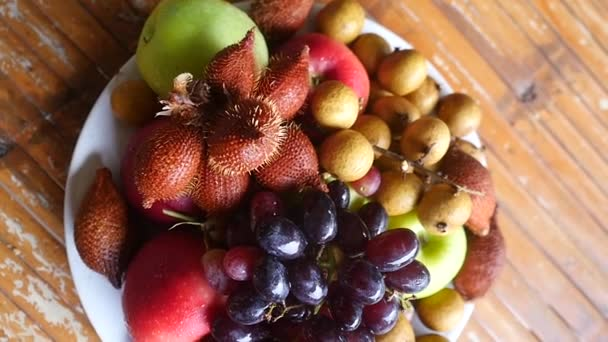 Top of view of delicious and arranged tropical fruit in bowl on a wooden table. slow motion. 1920x1080