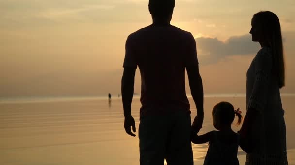 Silhouettes of happy family at sunset. Father, mother and daughter. Dad and mum keep daughters hand. slow motion. 1920x1080, hd