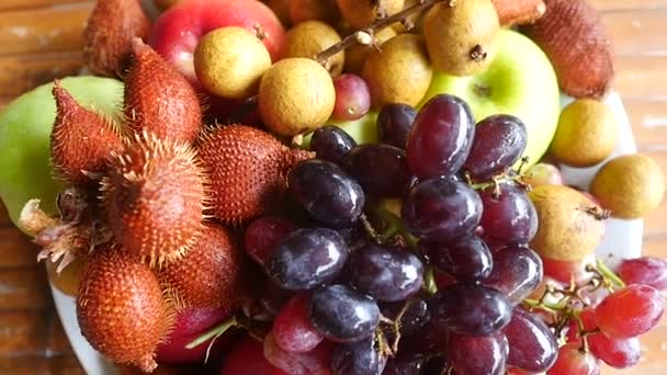 V horní části zobrazení mokré lahodné a uspořádány tropického ovoce v misce na dřevěný stůl. Zpomalený pohyb. 1920 × 1080