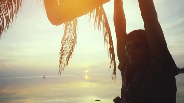 Young happy man in sunglasses hangs on a palm tree at amazing sunset on the beach. slow motion. 1920x1080