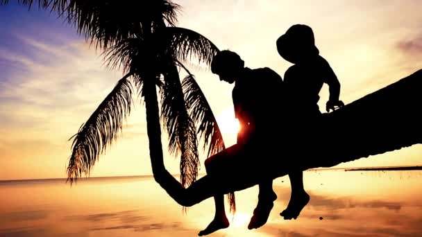 Silhouette of young happy father with his daughter sit on a palm tree during beautiful bright sunset. Having fun on summer happy family vacation. slow motion. 1920x1080