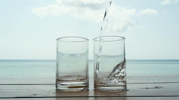 Voda se nalije do sklenice proti moři na tropické pláži. Zpomalený pohyb. 1920 × 1080