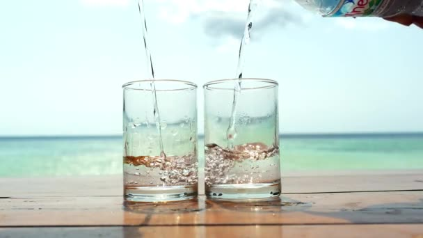 Clear water is poured into a glasses against the sea on tropical beach. 3840x2160