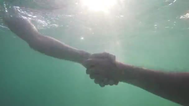 Dva podnikatelé potřást rukou pod vodou přes slunce. zblízka. 1920 × 1080