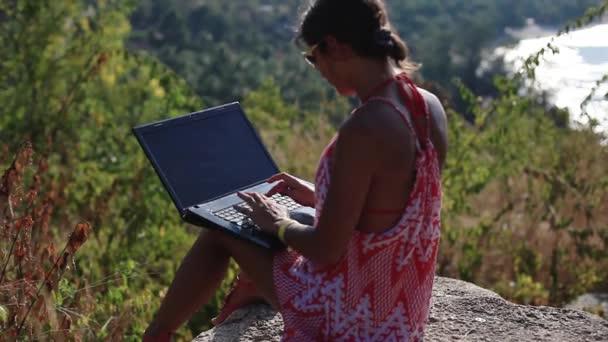 Üzletasszony befejező munka laptop, és pihentető a sziklákon. 1920 x 1080