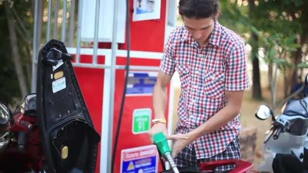 Man use gas pump nozzle filling gasoline fuel to tank of motorcycle in oil station. Thailand. 1920x1080