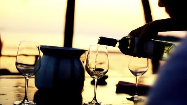 Nalil bílé víno ve skle na úžasný západ slunce s výhledem na moře v plážové restauraci. 1920 × 1080