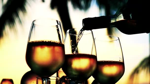 Pouring white wine in glass in slow motion at amazing sunset with sea view in a beach restaurant. Close up. 1920x1080
